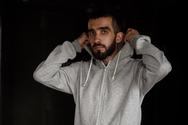 Jeune homme beau de mode avec la barbe dans le hoodie gris image libre de droits