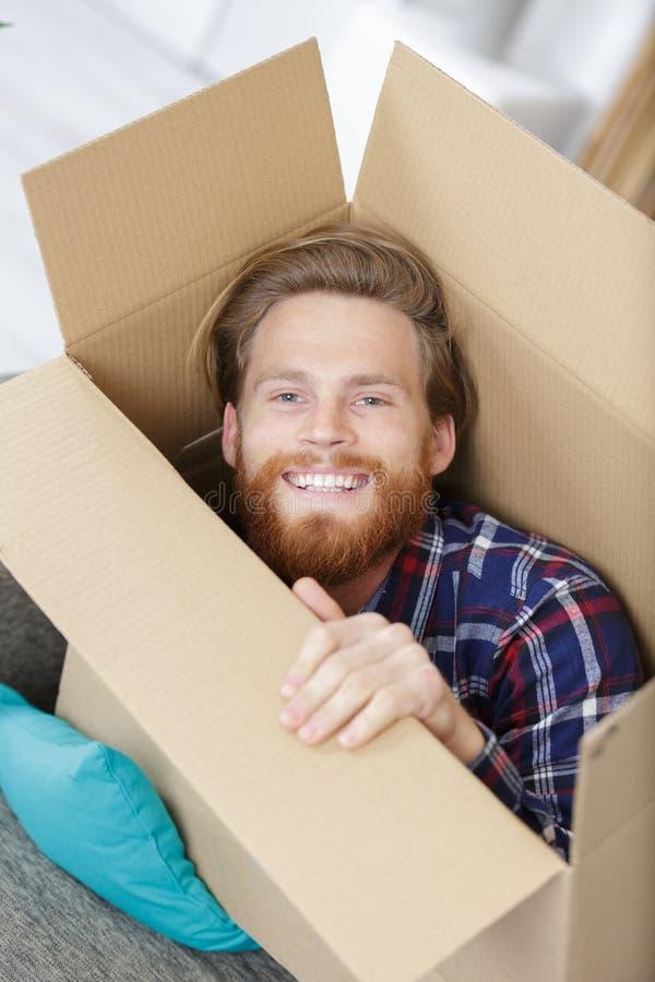 Jeune homme beau de portrait à l'intérieur de cardbox photo stock