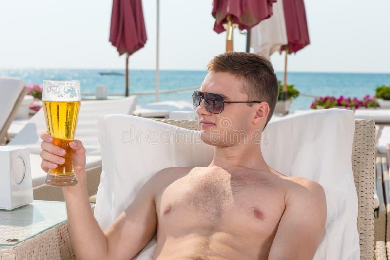 Jeune homme beau de sourire appréciant une bière photographie stock libre de droits
