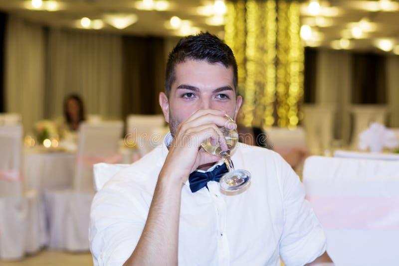 Jeune homme beau de sourire avec le verre de vin à disposition image stock