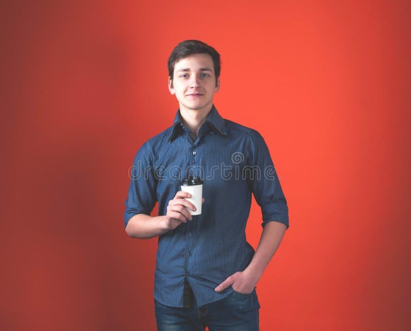 Jeune homme beau de sourire dans la chemise bleue avec la main dans la poche regardant la caméra photo stock