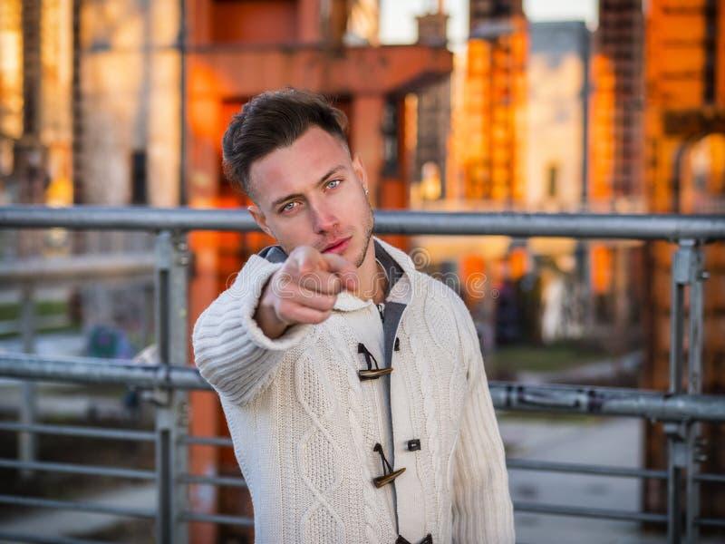 Jeune homme beau dirigeant des doigts à vous photo stock