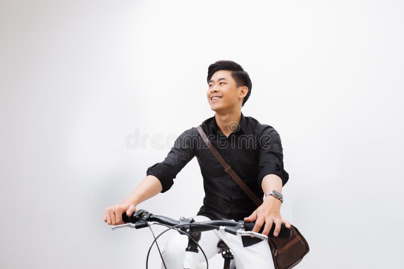 Jeune homme beau ?l?gant avec la bicyclette regardant loin d'isolement sur le blanc photographie stock libre de droits