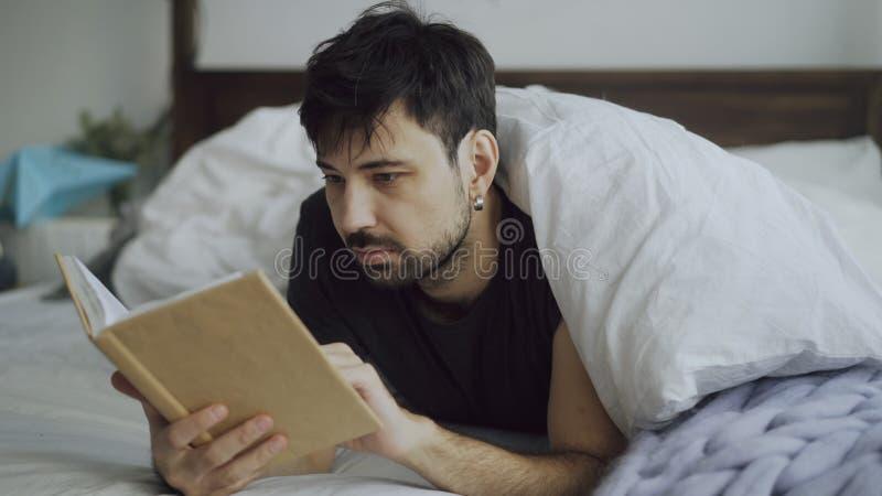 Jeune homme beau lisant un livre se situant dans le lit sous la couverture à la maison photo stock