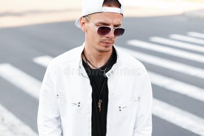 Jeune homme beau moderne de hippie en verres ronds à la mode dans une veste blanche d'été dans une casquette de baseball à la mod photos stock