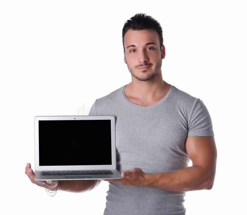 Jeune homme beau montrant l'ordinateur portable photo stock