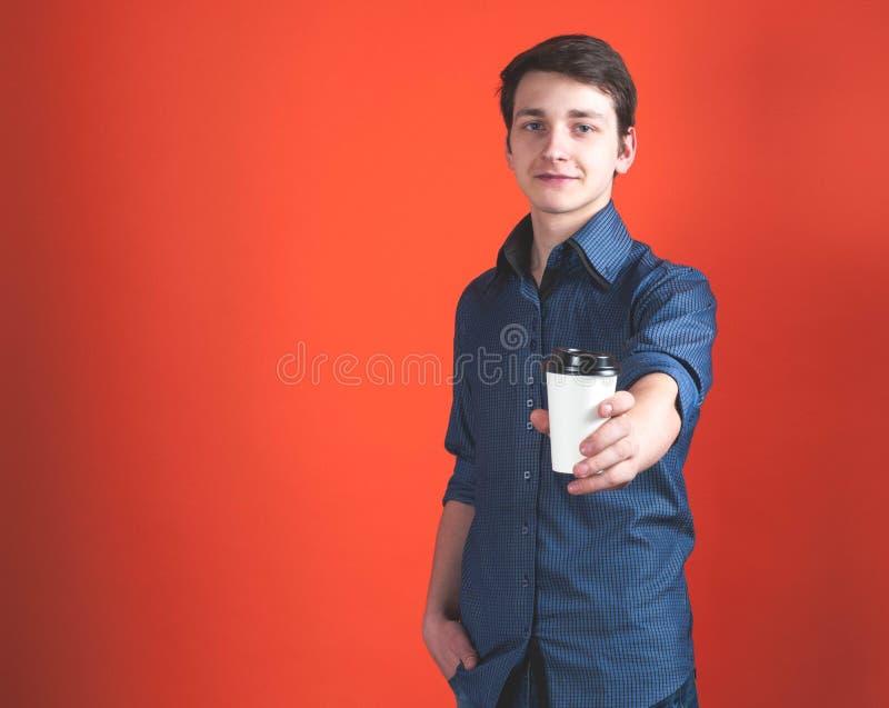 Jeune homme beau montrant la tasse de papier dans la main tendue et regardant la caméra images stock