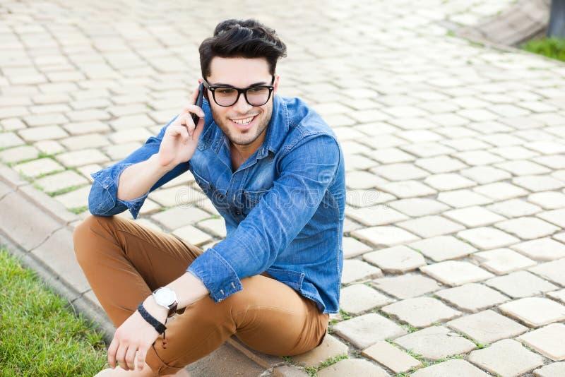 Jeune homme beau parlant sur un smartphone photo stock