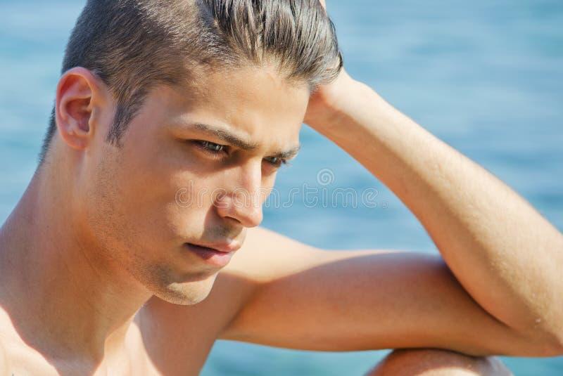 Jeune homme beau pensant à côté de la mer photos stock