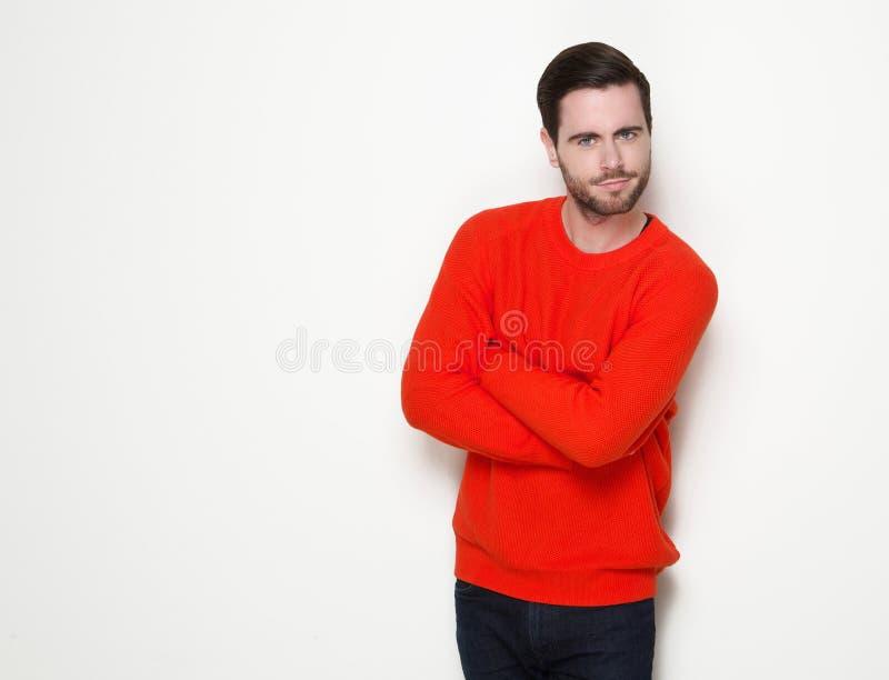 Jeune homme beau posant avec des bras croisés photographie stock libre de droits