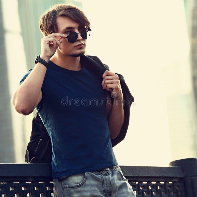 Jeune homme beau posant en verres de soleil de mode et jugeant images stock