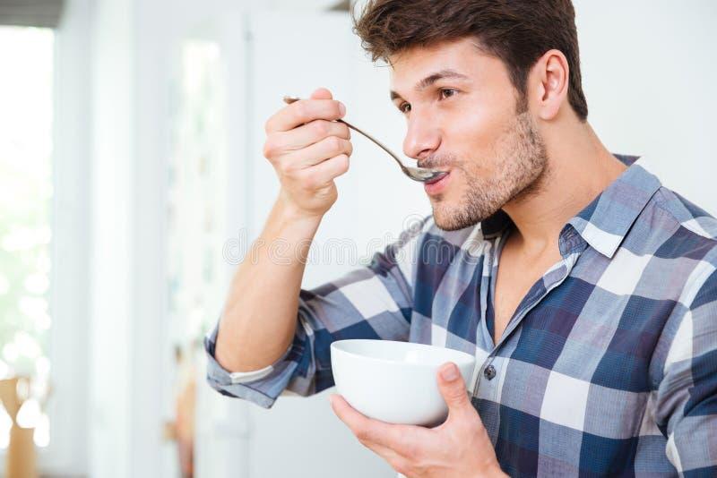 Jeune homme beau prenant le petit déjeuner à la maison photos stock