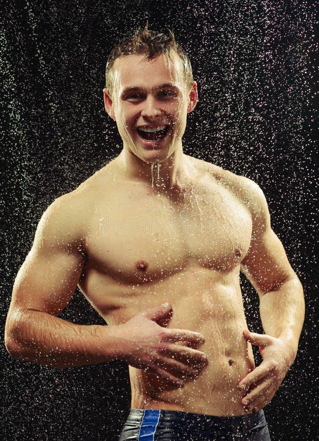 Jeune homme beau prenant une douche image stock