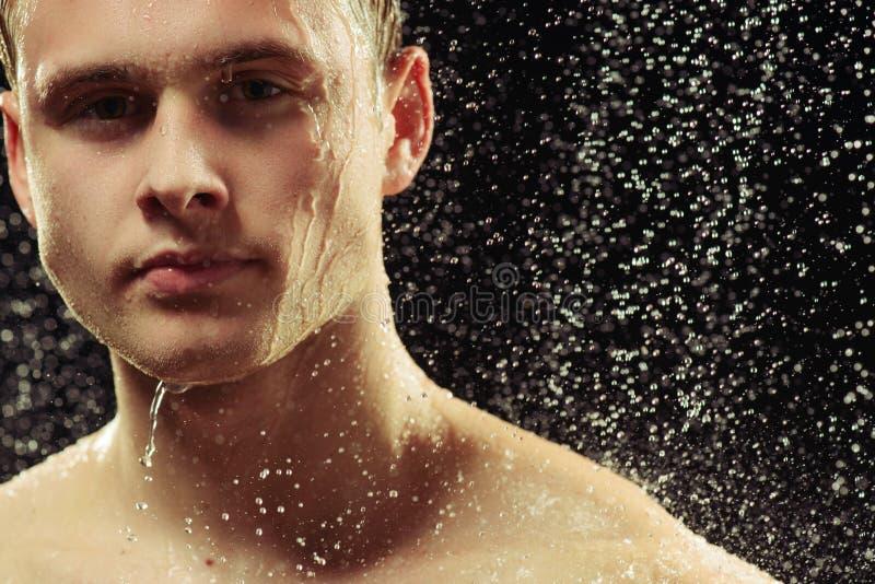 Jeune homme beau prenant une douche photos stock