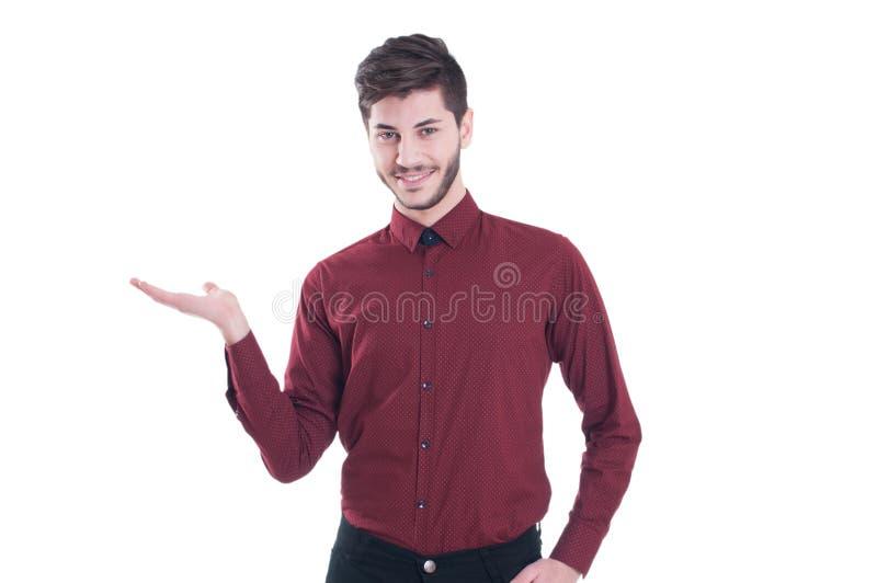 Jeune homme beau regardant l'appareil-photo et tenant l'espace de copie photo libre de droits