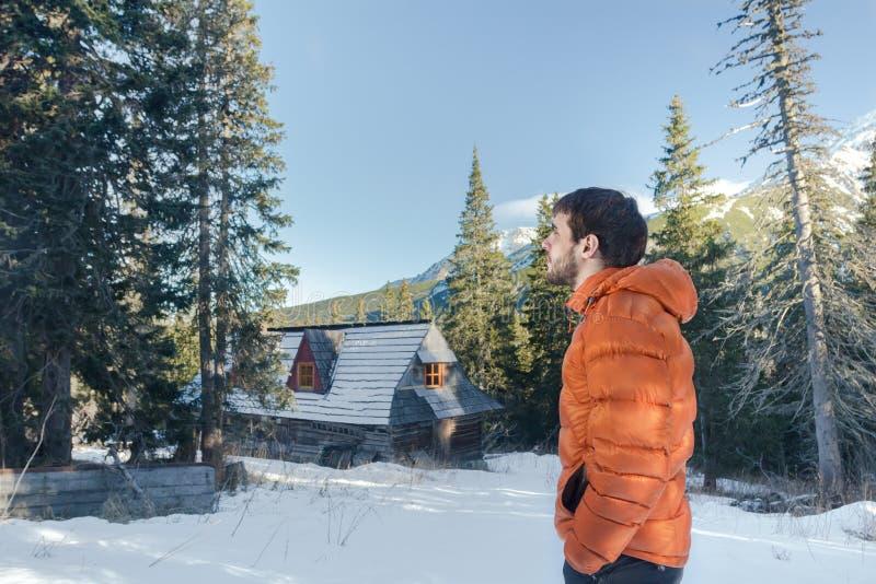 Jeune homme beau regardant la vue étonnante en vallée avec la hutte de montagne et la forêt de conifère images stock