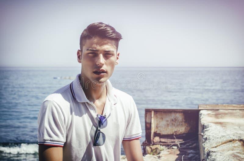 Jeune homme beau s'asseyant à côté de la mer photographie stock