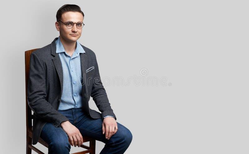 Jeune homme beau s'asseyant sur la chaise photo libre de droits