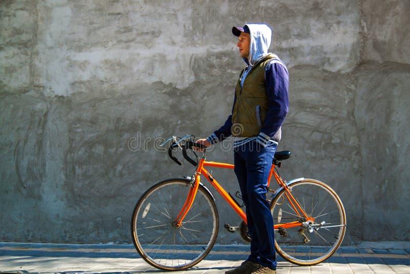 Jeune homme beau s'asseyant sur le vélo et smilling dans la ville photo stock