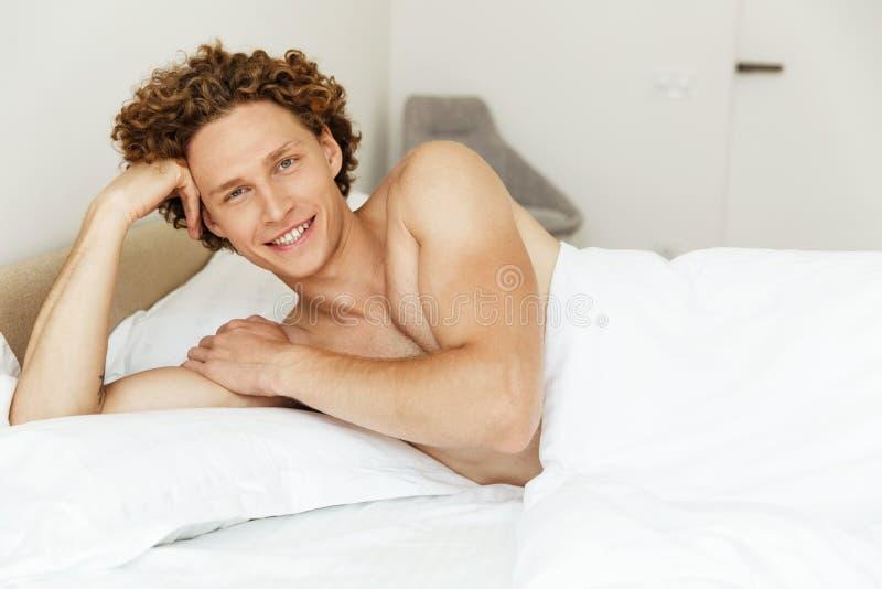 Jeune homme beau se situant dans le lit et regardant l'appareil-photo photo libre de droits