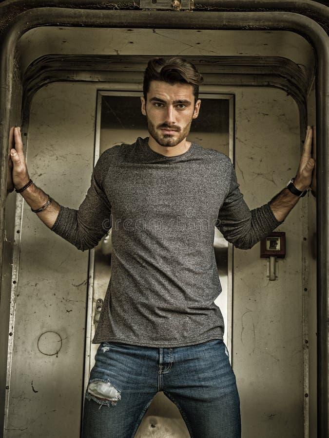 Jeune homme beau se tenant dans la station photo libre de droits