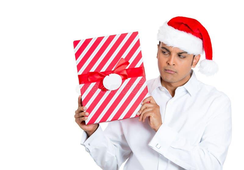 Jeune homme beau secouant et écoutant le cadeau enveloppé photos libres de droits