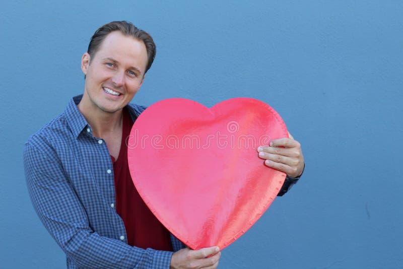 Jeune homme beau tenant le grand symbole rouge de coeur sur le fond bleu image stock