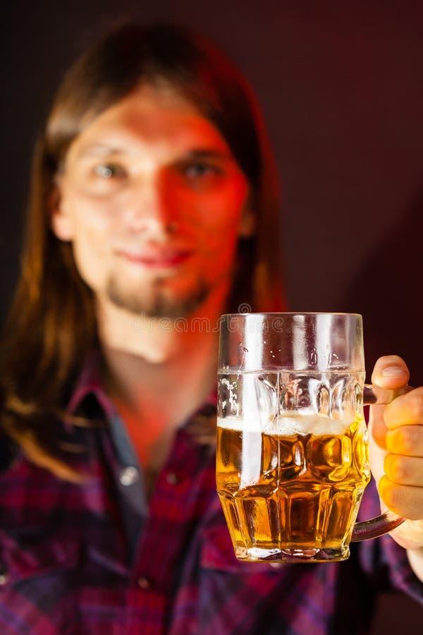 Jeune homme beau tenant une tasse de bière photo stock
