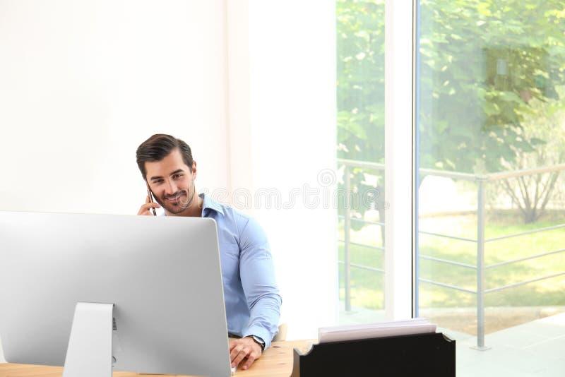 Jeune homme beau travaillant avec et ordinateur à la table dans le bureau images stock