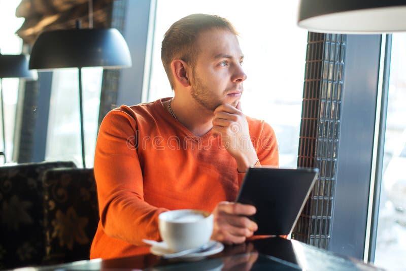 Jeune homme beau travaillant avec le comprimé, pensée, regardant la fenêtre, tout en appréciant le café en café photographie stock
