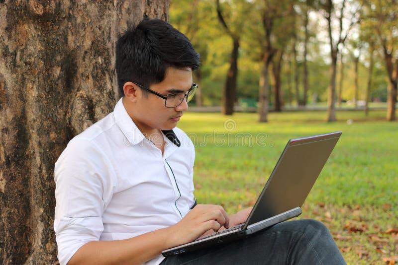 Jeune homme beau travaillant avec un ordinateur portable à l'arrière-plan brouillé de nature photo stock