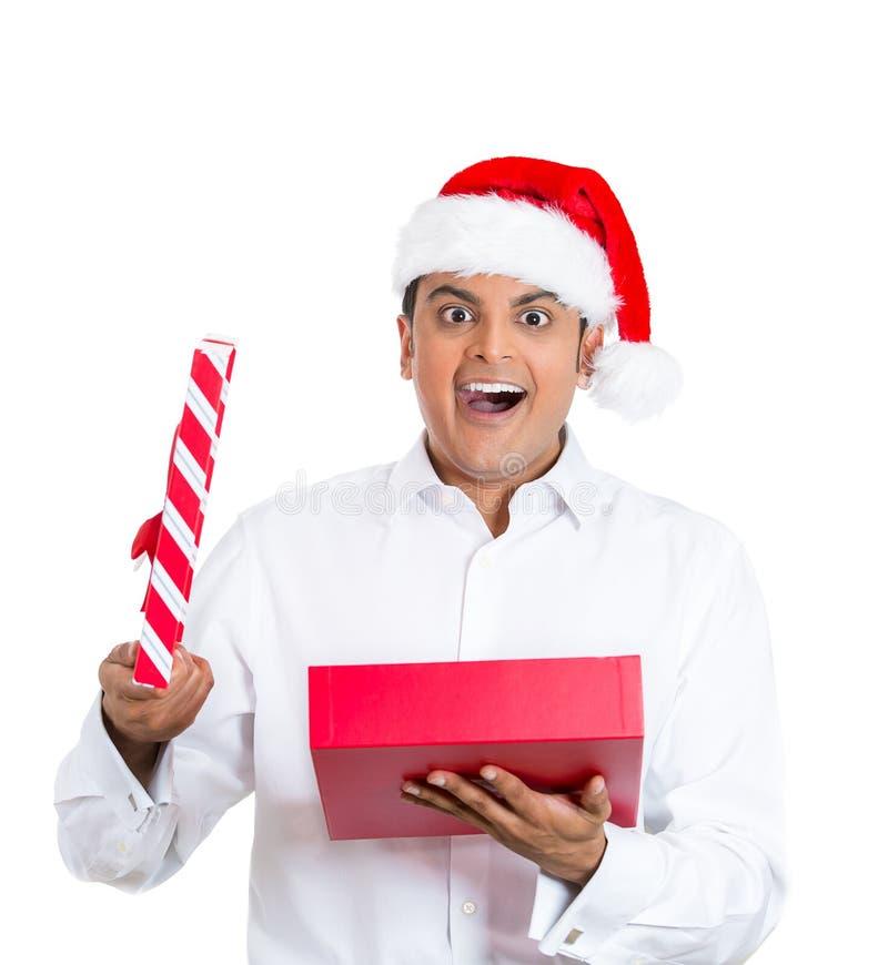 Jeune homme beau utilisant le chapeau rouge du père noël, chemise, cadeau et heureux s'ouvrants images libres de droits