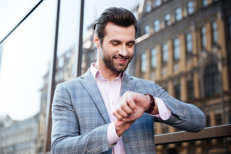 Jeune homme beau vérifiant le temps sur sa montre-bracelet images stock