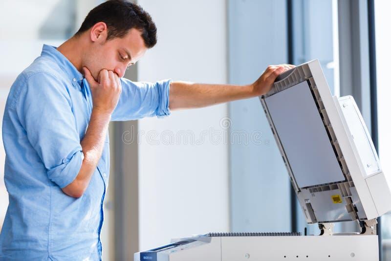 Jeune homme bel à l'aide d'une machine de copie photographie stock