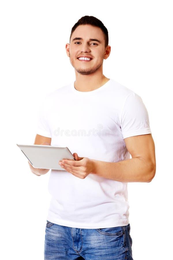 Jeune homme bel à l'aide du comprimé image stock