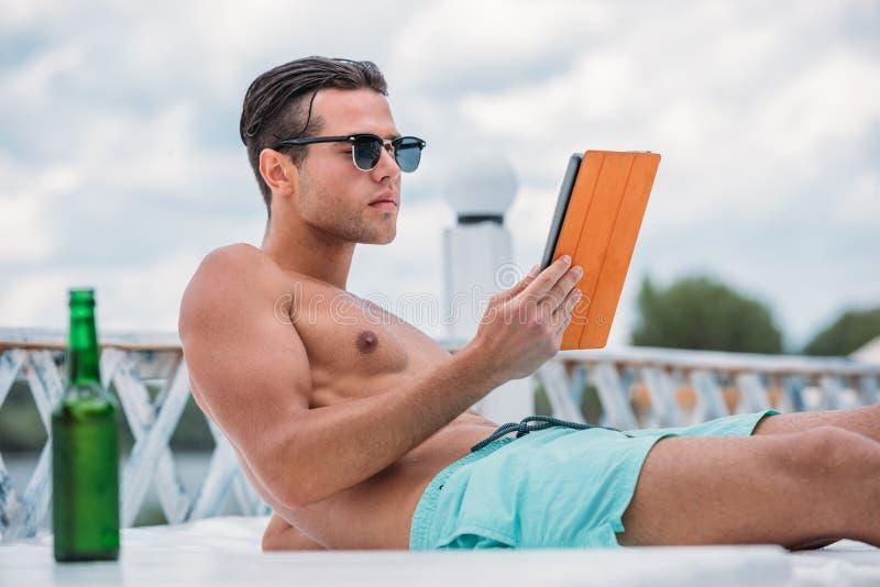 Jeune homme bel à l'aide du comprimé tout en se trouvant sur le piscine-lit photo stock