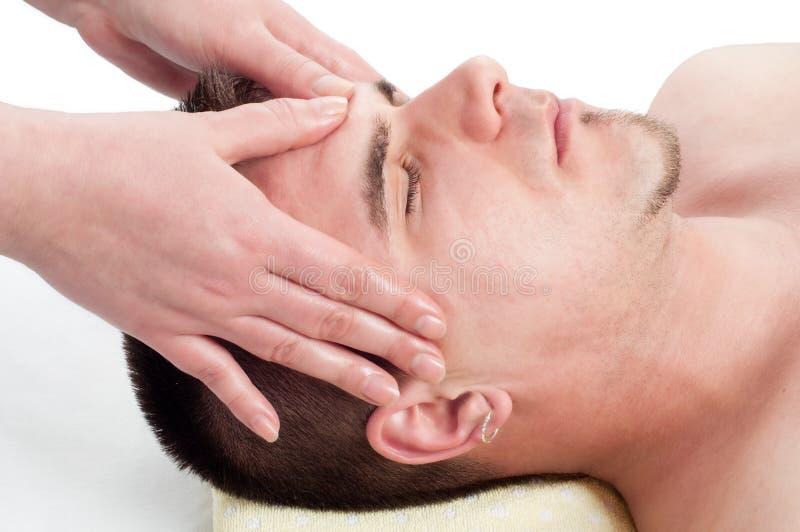 Jeune homme bel appréciant le massage facial photos stock
