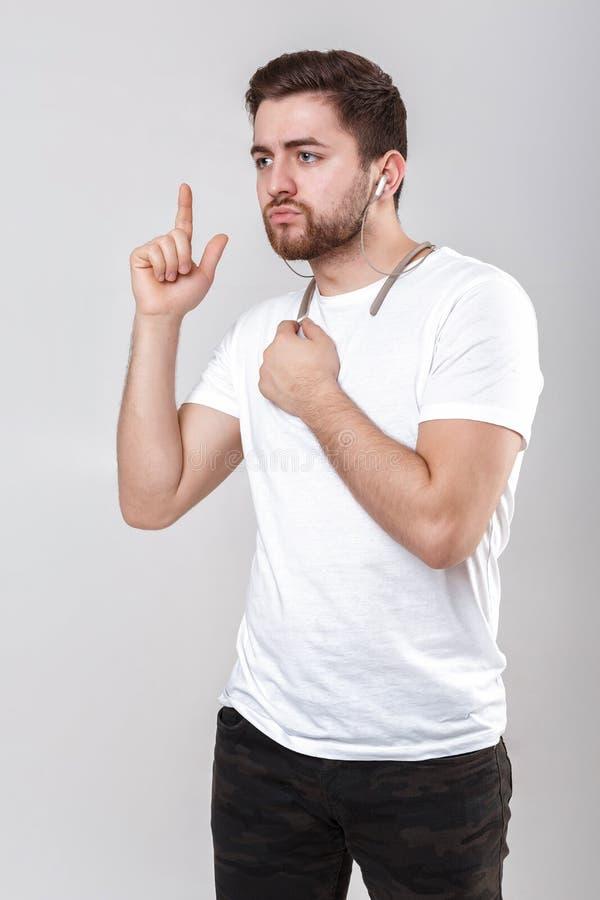 Jeune homme bel avec la barbe dans le T-shirt écoutant la musique sur des écouteurs image libre de droits