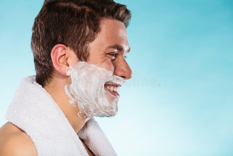 Jeune homme bel avec la mousse de crème à raser images stock