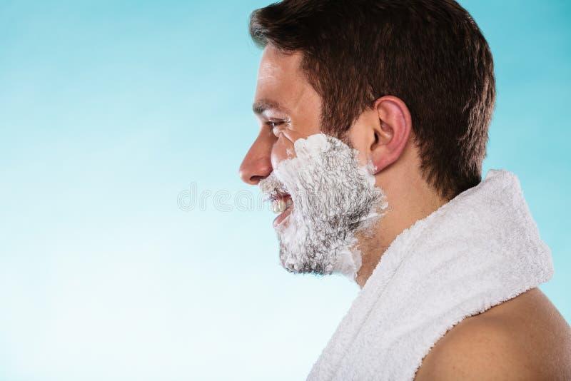 Jeune homme bel avec la mousse de crème à raser photos stock