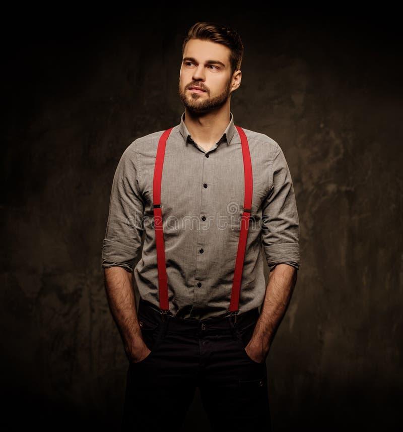 Jeune homme bel avec les bretelles de port de barbe et pose sur le fond foncé photo libre de droits