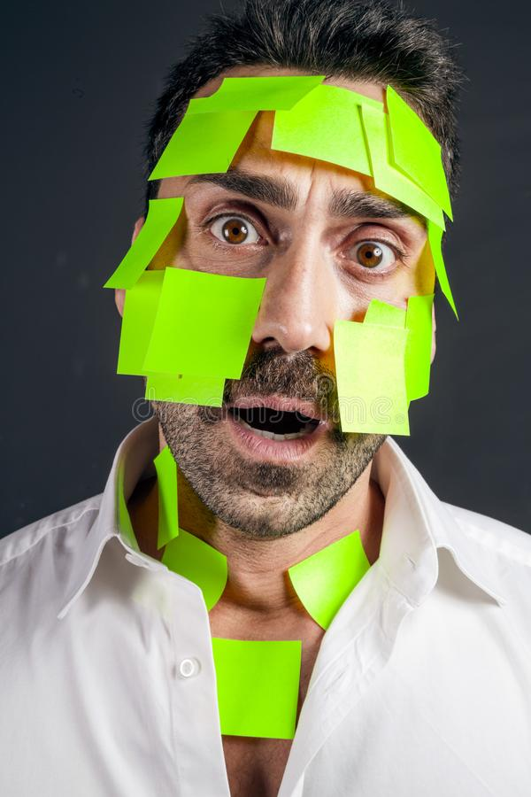 Jeune homme bel avec les notes collantes sur son visage photos stock