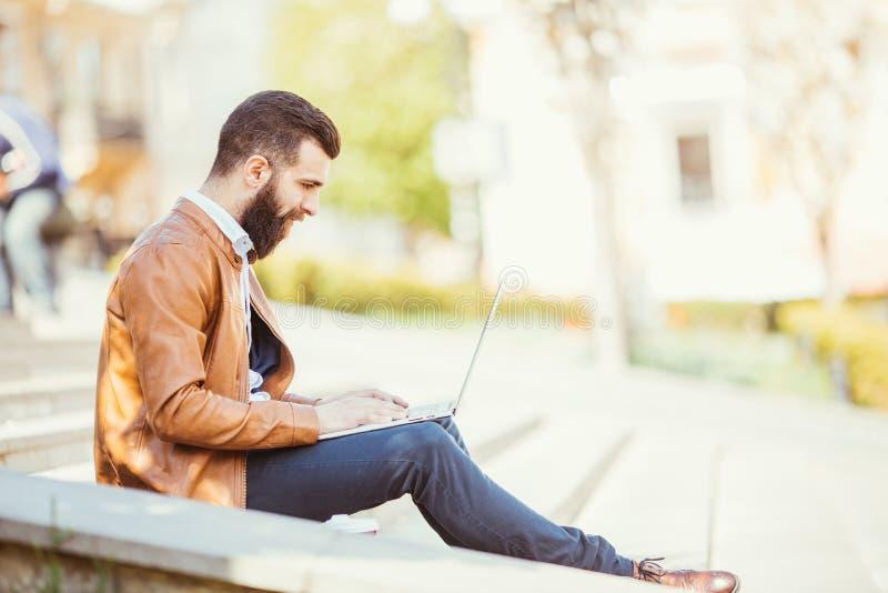 Jeune homme bel barbu s'asseyant sur les escaliers utilisant l'ordinateur portable dans la ville photos stock