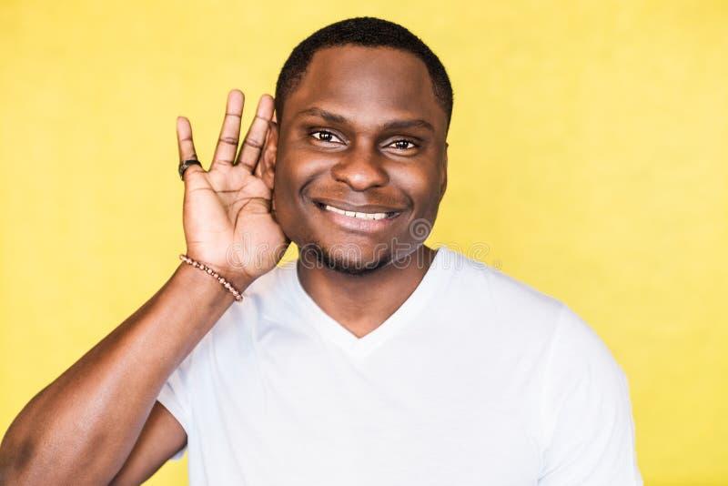 Jeune homme bel d'Afro-américain essayant d'entendre meilleur en attachant sa paume à l'oreille images stock
