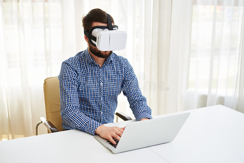 Jeune homme bel dans le fonctionnement en verre de réalité virtuelle sur son recouvrement photos stock