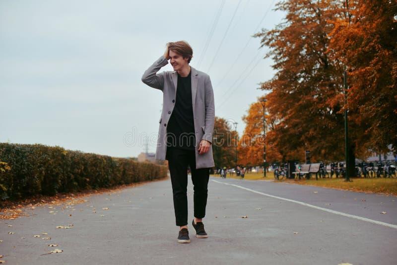 Jeune homme bel dans le manteau Homme bien habillé à la mode posant dans le manteau élégant Garçon sûr et focalisé extérieur à l' photos libres de droits