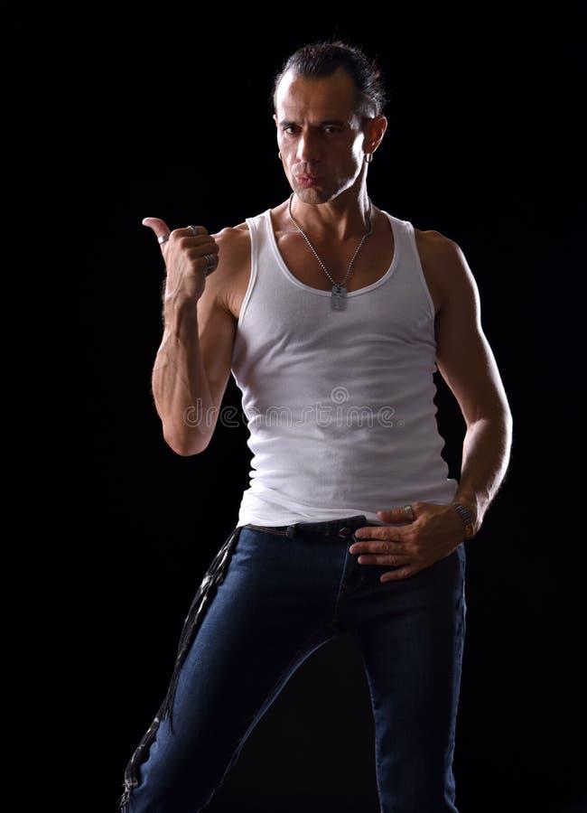 Jeune homme bel dans le T-shirt et des jeans blancs image stock
