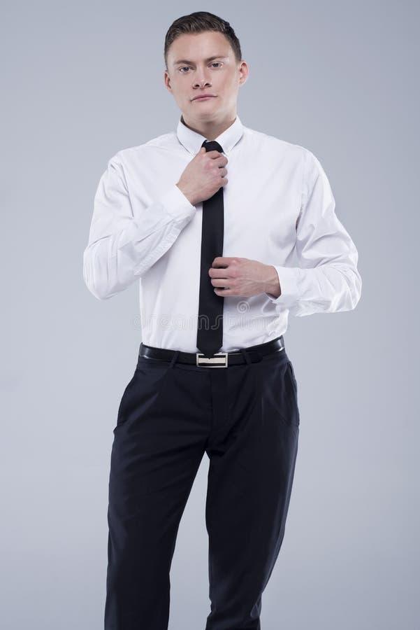 Jeune homme bel dans une chemise avec un lien sur un fond gris-clair photo libre de droits