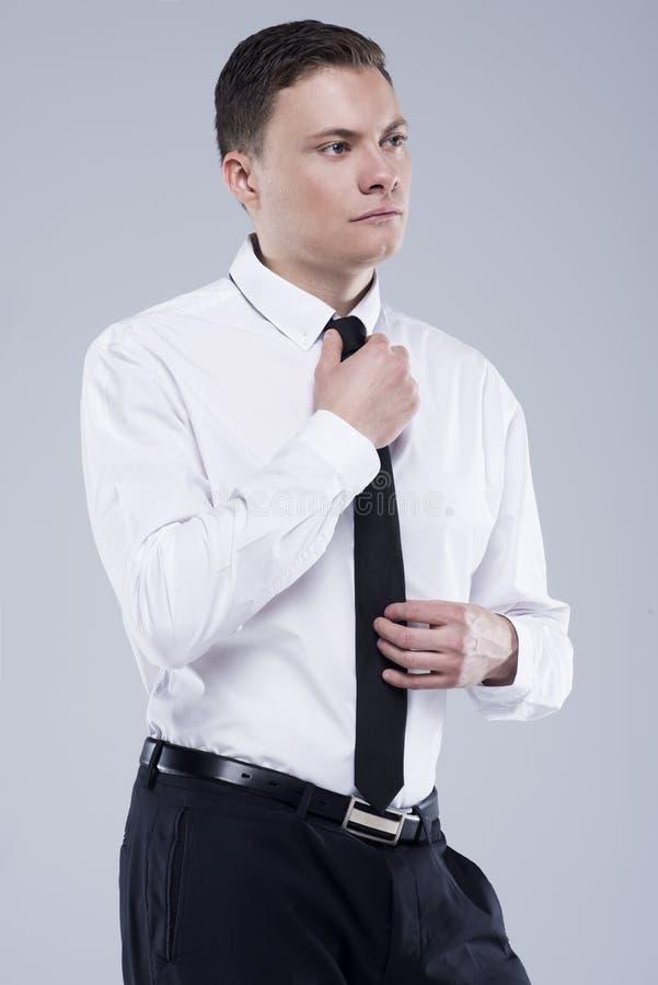 Jeune homme bel dans une chemise avec un lien sur un fond gris-clair image stock