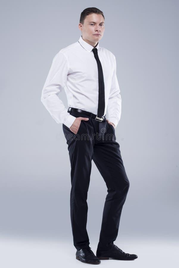 Jeune homme bel dans une chemise avec un lien sur un fond gris-clair photos libres de droits